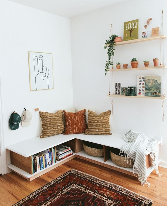 corner with wooden floorw, white wall, white bench, pillows, floating shelves, bookshelves under