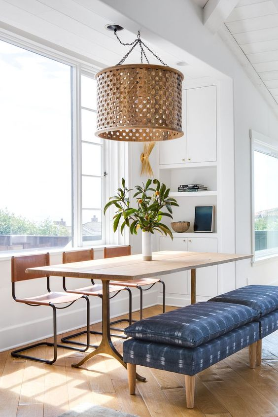 dining area, wooden herringbone pattern, wooden table, wooden chairs, wooden covered pendant, bench with blue cushion, white built in shelves, windows