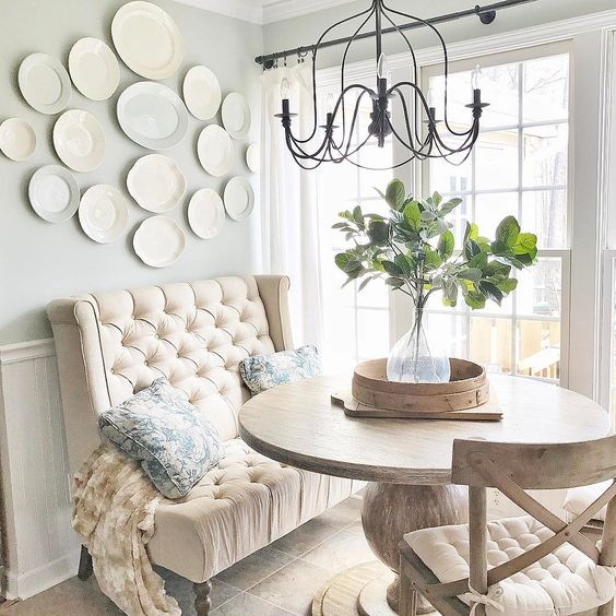 dining nook, brow tiles, wooden round table, wooden chairs with white cushion, white blue wall, beige short sofa, chandelier, window