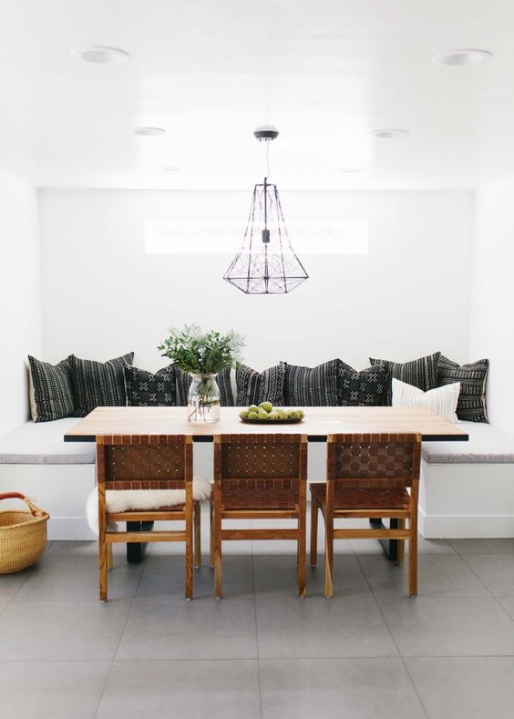 dining nook, grey floor tiles, white corner bench, off white thin cushion, black pillows, geometrical wire pendnat, wooden table