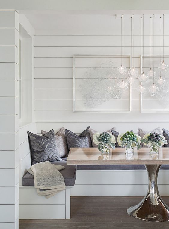 dining nook, wooden floor, white bench with grey cushion, pillows, white wooden planks wall, glossy table, glass pendants