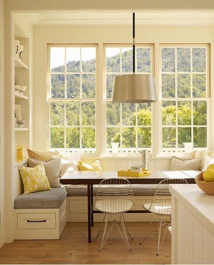 dining nook, wooden floor, white corner bench, grey cushion, yellows, white grey pillows, wooden table, white chairs, silver covered pendant