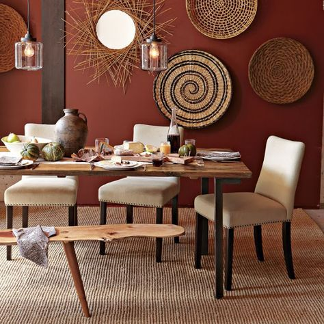 dining room, rug, white chairs, wooden table, wooden bench, marroon wall, rattan wall decorations