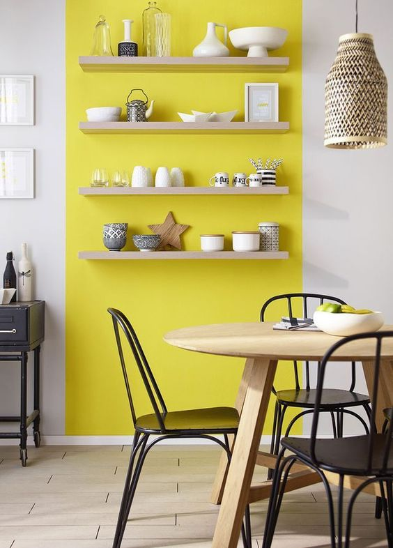 dining room, white wall, wooden floor, wooden table, black emtal chairs, yellow accent on the wall, foating shelves