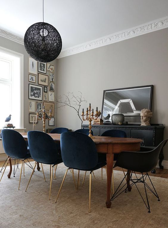 dining room, wooden floor, brown rug, black velvet chairs, wooden long curvy table, black pendant, beige wall, black cabinet