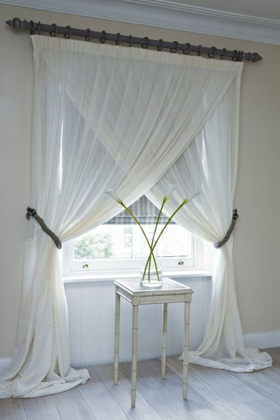double white curtain opened in two different ways for a clear glass window