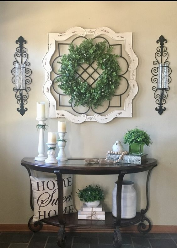 entrance with half round wooden table with metal support, wall decoration, sconces, pillows, vase