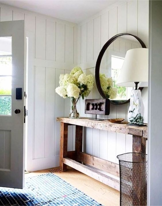 entrance with wooden simple basic table, vases with flowers, round mirror, table lamp