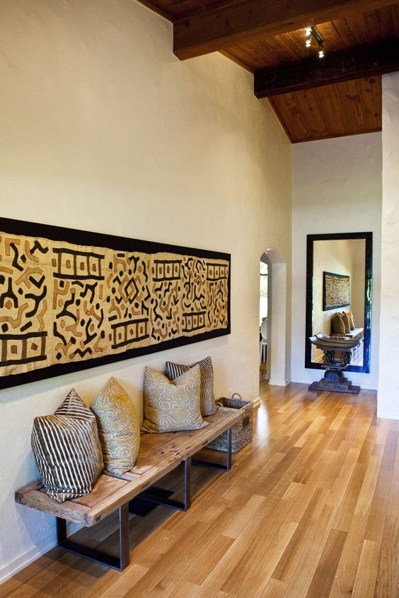 entrance, wooden floor, wooden low bench, tribal painting, white wall, wooden ceiling with beams, mirror, wooden round side table