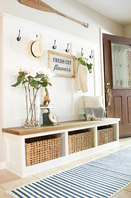 entry ways with white bench with brown wooden top, shelves under, basket inside the shelves, hooks, decoratoion