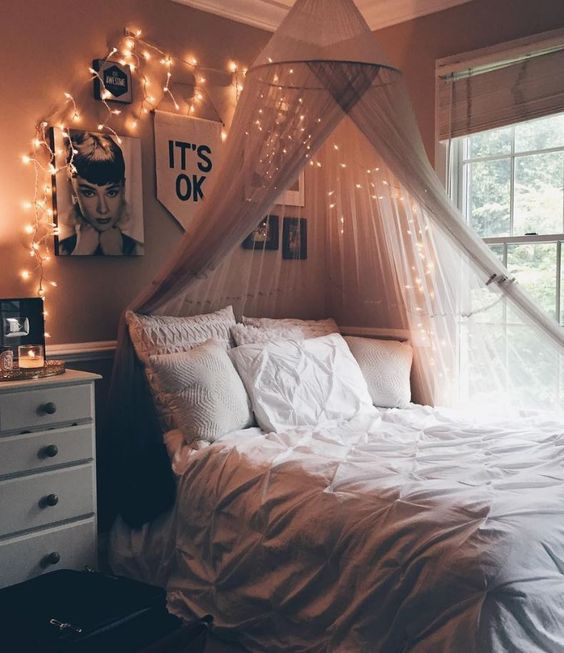 fairy lights among the picture on the wall above the head board