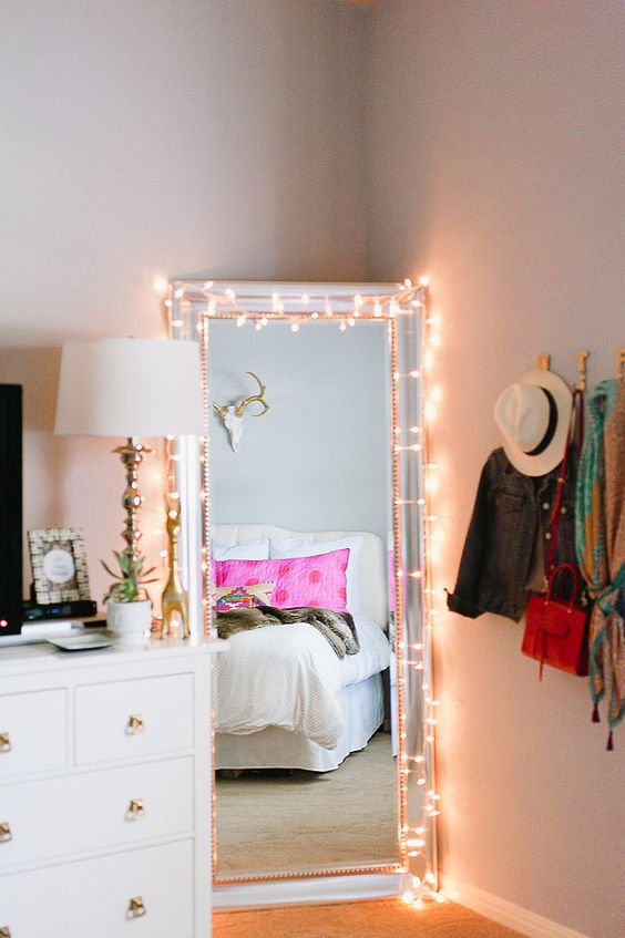 fairy lights around the square mirror on the floor of a bedroom