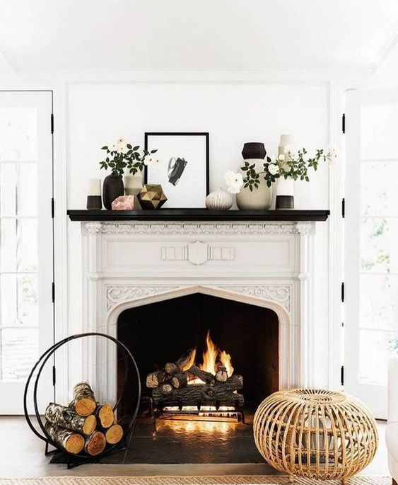 fireplace in a room with wooden floor, rug, woo on rack, white wall, white frame on fireplace with arch