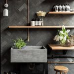 Grey Bathroom Vanity With Grey Herringbone Pattern On Floor And Wall, Wooden Floating Shelves, Wooden Stool, White Sconces