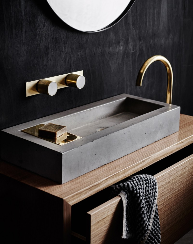 grey sink on wooden vanity cabinet, dark wall, golden faucet