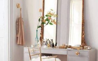grey table with large golden framed mirror, golden thin chair with white faux fur