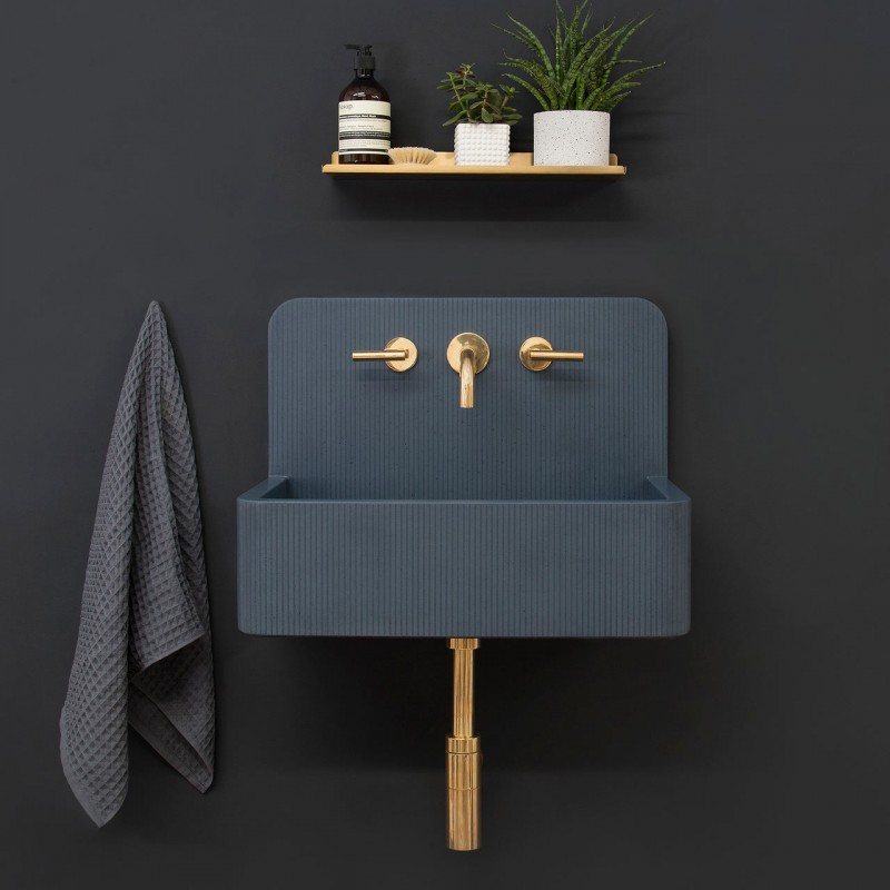 grey wall, grey vanity with golden faucet and pipe, small wooden floating shelf
