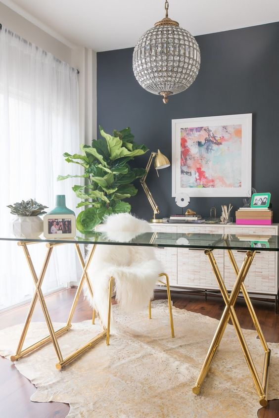 home office with wooden floor, faux animal skin rug, glasss table with golden metal legs, white chair, grey wall, golden lamp