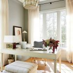 Home Office With Wooden Floor, White Wooden Table, White Ottoman, Grey Chair, Grey Wall, Chandelier, Table Lamp, Wide Windows With Curtain