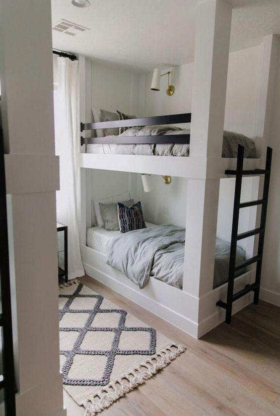 kids bunk bed with white wooden posts, grey bedding, wlack wooden fence for the top bed, white rug, wooden flooring