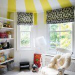 Kids Room With White Rug Flooring, White Floating Shelves, Heater, White Floor Lamp, Shades On Windows, Yellow White Stripes Motive