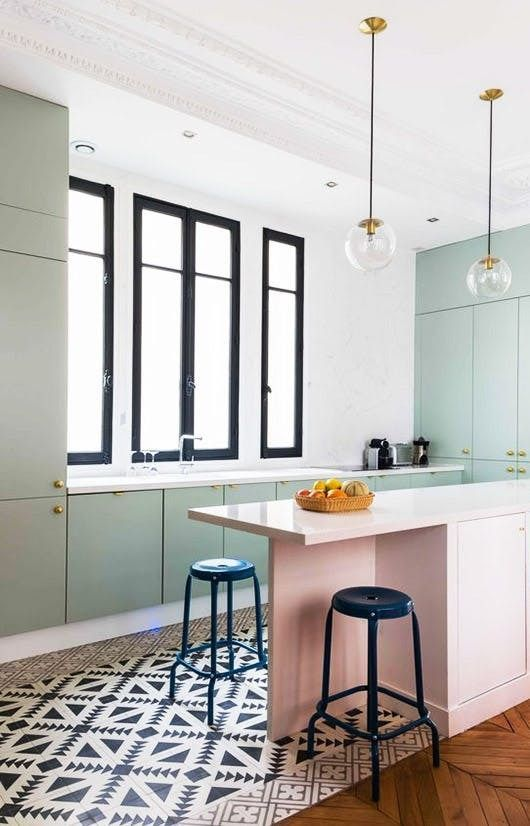 kitchen with black and white patterned tiles, mint green cabinet and cupboards with white counter top, pink island with blue stoo;, glass pendant, white wall