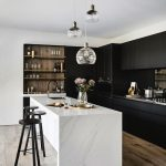 Kitchen With Black Cabinet, Wooden Floor, White Marble Island, Wooden Wine Shelves, Black Stool