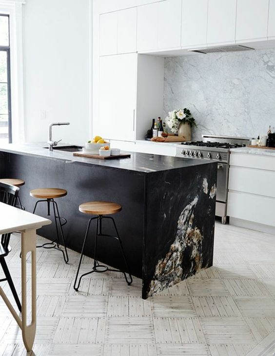 kitchen with black marble top on the black island, stool, white marble bacsplash, white cabinet, white light tiles