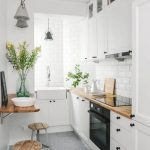 Kitchen With Grey Floor Tiles, White Cabinet, White Subway Backsplash, Wooden Countertop, Wooden Small Floating Table With Wooden Stool, Sink On The Corner