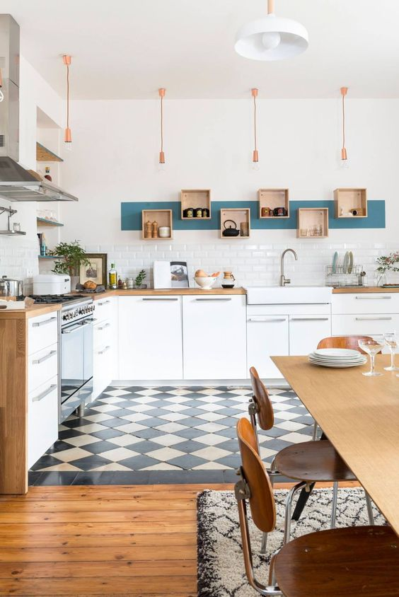kitchen with plaid pattern floor, white cabinet under wooden counter top, white tiles wall, boxes with interesting placement on the wall