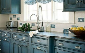 kitchen with tiles floor, blue wooden cabinet with silver knobs, dark blue marble top, white windows with blue curtains, white and blue backsplash