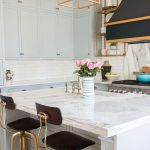 Kitchen With White Cabinet, White Tiles Backsplash, White Island With White Marble Countertop, Marble Back Wall For The Stove