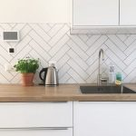 Kitchen With White Cabinet, Wooden Counter Top, White Wall, White Rectangular Tiles In Herringbone, White Cupboard
