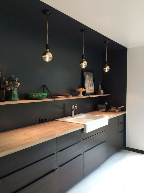 kitchen with white floor, black cabinet under wooden counter top, black wall and some of the ceiling, open shelves