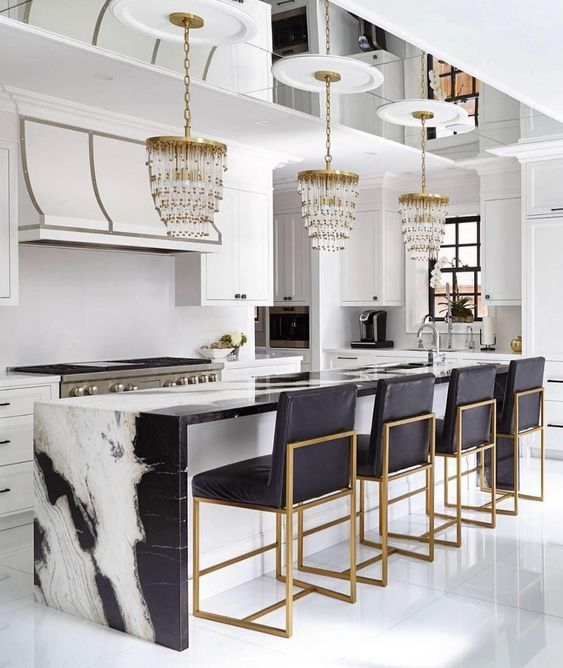 kitchen with white floor, white cabinet and wall, white and black marble island, black chairs with golden support
