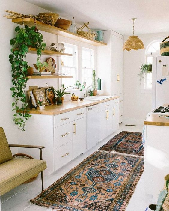 kitchen with white flooring, rug, white cabinet, wooden kitchen top, wooden floating shelves, white cupboard, rattan pendant