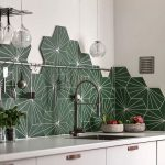 Kitchen With White Wall, White Cabinet, White Counter Top, Green Geometric Tiles On Backsplash, Silver Faucet