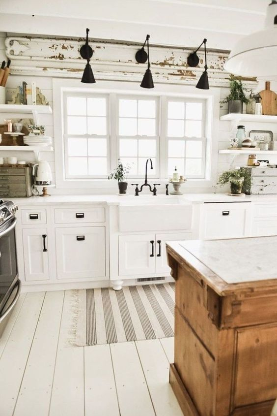 kitchen with white wooden floor, white wall, white wooden cabinet, white wooden open shelves, wooden island with white top, black faucet, knobs, sconces