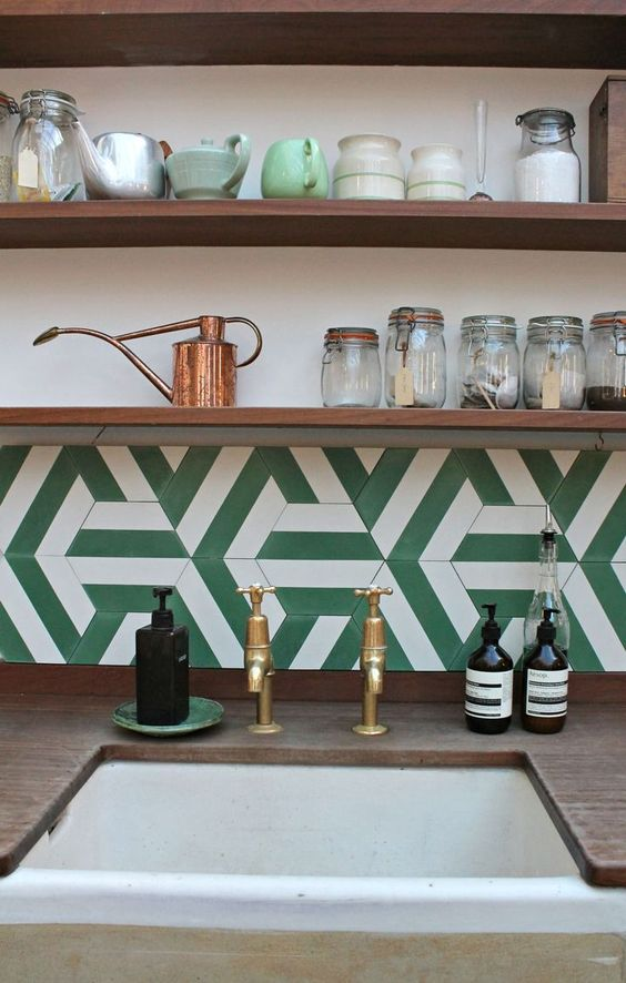 kitchen with wooden counter top, white sink, brown wooden shelves, white green geometric backsplash
