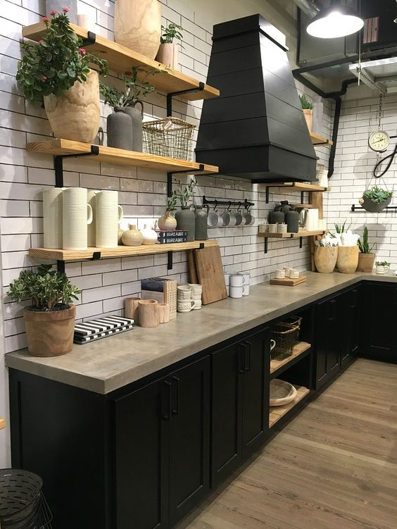 kitchen with wooden floor, black cabinet underr marble counter top, white subway tiles on the wall, wooden open shelving