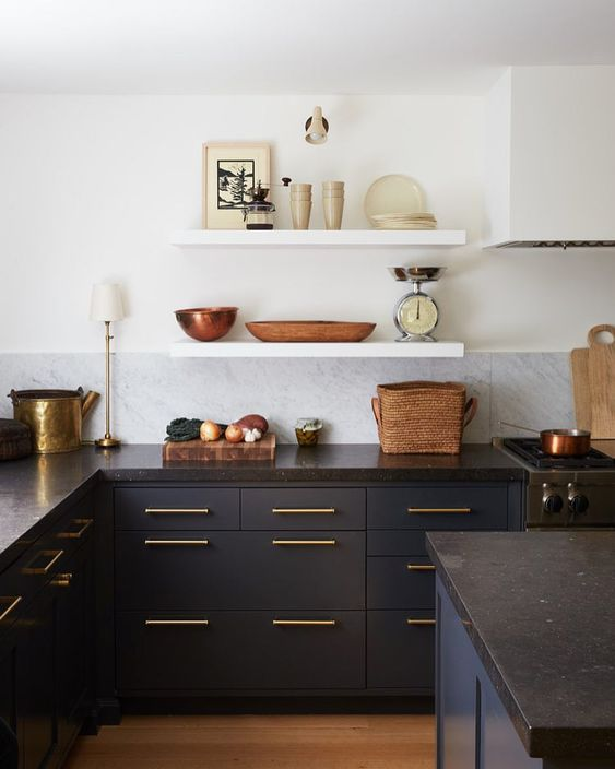 kitchen with wooden floor, black cabinet with golden handles, white tiles backsplash, white walls with white open shelves, black wooden island with black top