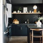 Kitchen With Wooden Floor, Black Island With Wooden Chairs, Black Cabinet, Black Herringbone Backsplash, Wooden Open Shelves