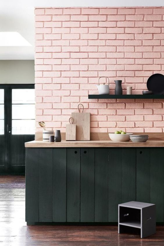 kitchen with wooden floor, black wooden cabinet under wooden counter top, pink painted open brick wall, black painted wooden shelf