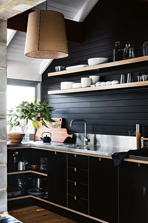 kitchen with wooden floor, black wooden wall, black cabinet, silver counter top, wooden open shelves, brown covered pendant