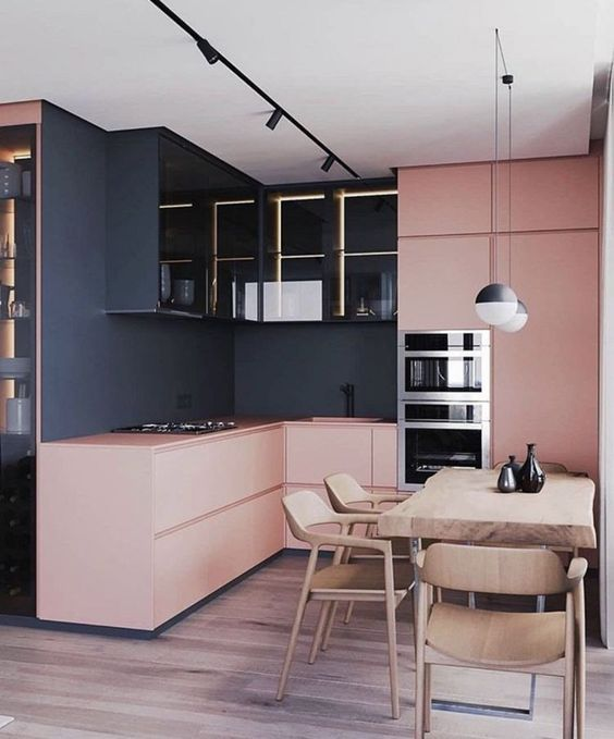 kitchen with wooden floor, pink cabinet and cupboards, black wall and black cabinet on top with glass door
