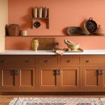 Kitchen With Wooden Floor, Rug, Warm Orange Cabinet, Orange Wall, White Counter Top, Wooden Shelves