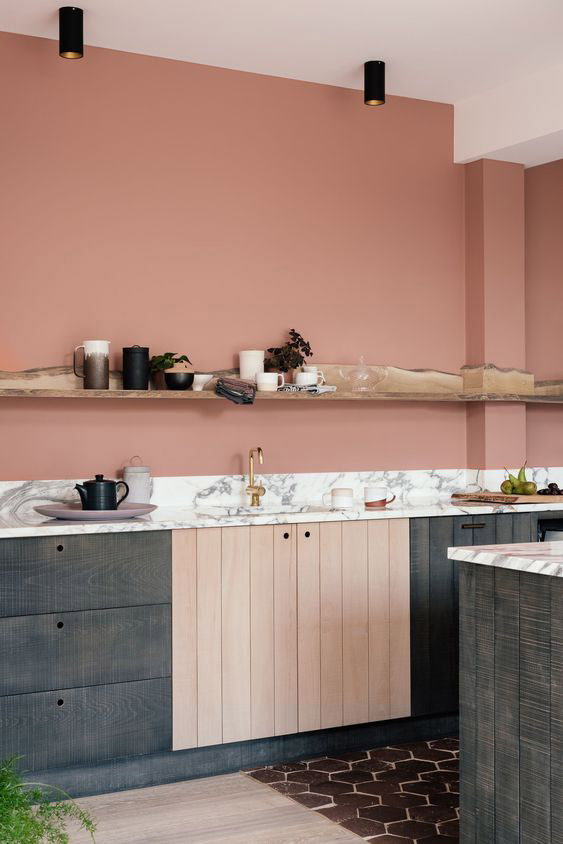 kitchen with wooden floor, tiles on the floor, grey wooden cabinet, brown wooden cabinet under the sink, white marble counter top, pink painted wall, wooden open shelves