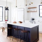 Kitchen With Wooden Floor, White Cabinet, White Subway Tiles Backsplash, Black Island With White Top, Round Dining Table With White Modern Chairs, Glass Pendant, Wooden Shelves