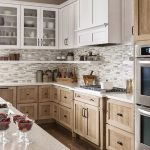 Kitchen With Wooden Flooring, Light Brown Wood Cabinet With Handles, White Grey Backsplash, White Wooden Floatin Cabinet, Island With White Top
