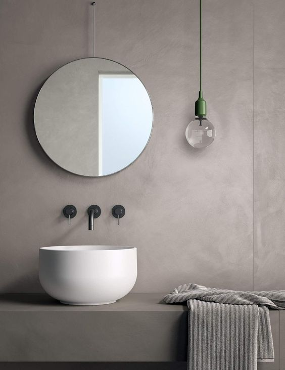 light grey bathroom vanity with grey vanity, white round sink, round mirror, grey wall with glass pendant accessory